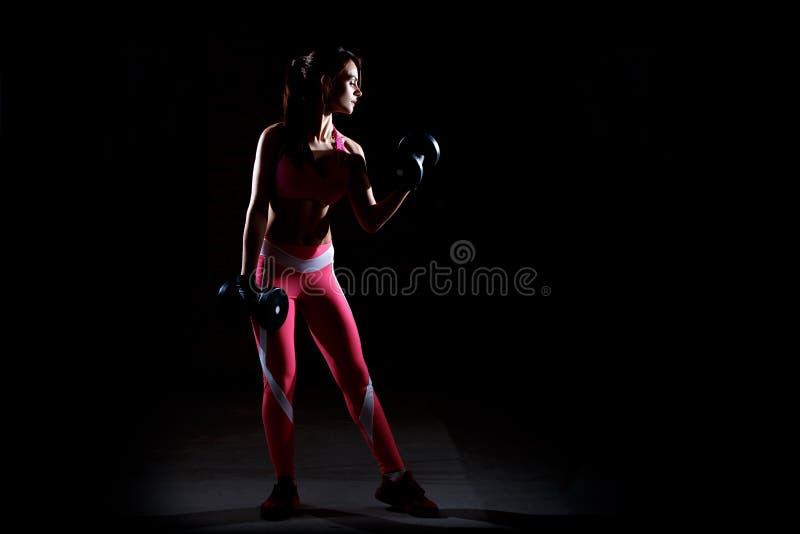 Σκοτεινή φωτογραφία αντίθεσης της νέας όμορφης γυναίκας ικανότητας που που εκπαιδεύει στη γυμναστική στοκ φωτογραφία με δικαίωμα ελεύθερης χρήσης