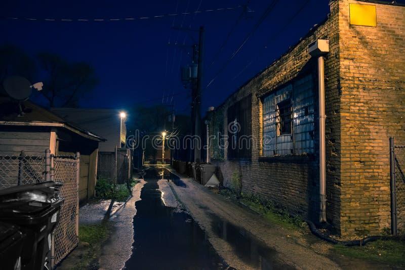 Σκοτεινή, χαλικώδης και υγρή βιομηχανική αλέα πόλεων τη νύχτα στοκ φωτογραφία με δικαίωμα ελεύθερης χρήσης