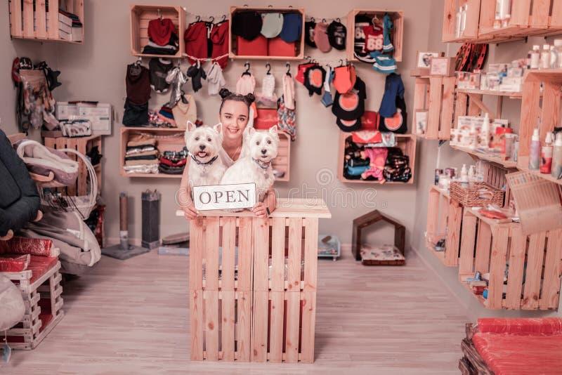 Σκοτεινός-μαλλιαρή γυναίκα που χαμογελά ανοίγοντας το κατάστημα για τα κατοικίδια ζώα στοκ φωτογραφία
