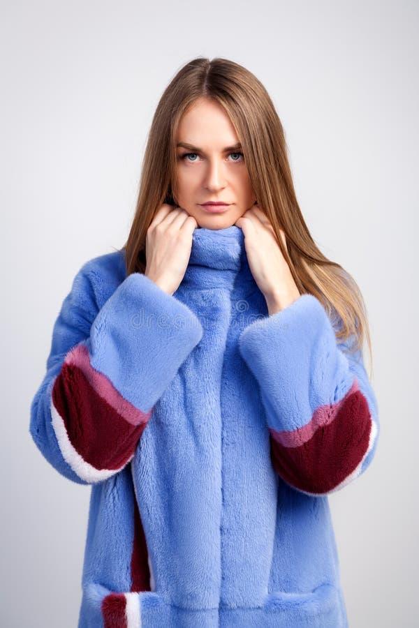 Σκοτεινός-μαλλιαρή γυναίκα σε ένα μπλε παλτό γουνών στοκ εικόνες