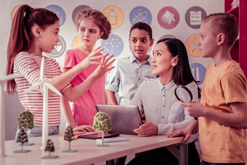 Σκοτεινός-μαλλιαρή θηλυκή συνεδρίαση δασκάλων με την ταμπλέτα της στοκ εικόνες με δικαίωμα ελεύθερης χρήσης