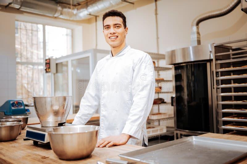 Σκοτεινός-μαλλιαρός αρχιμάγειρας που φορά την άσπρη ομοιόμορφη στάση στην κουζίνα στοκ εικόνες με δικαίωμα ελεύθερης χρήσης