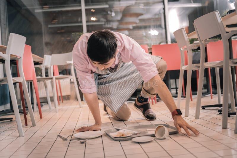 Σκοτεινός-μαλλιαρός σερβιτόρος που καθαρίζει το πάτωμα μετά από να ρίξει το δίσκο με τα τρόφιμα στοκ εικόνες