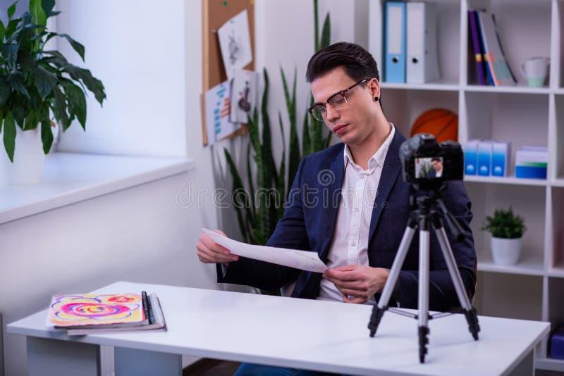 Σκοτεινός-μαλλιαρός τύπος που συγκεντρώνεται στο σχέδιο στο κομμάτι χαρτί στοκ εικόνες