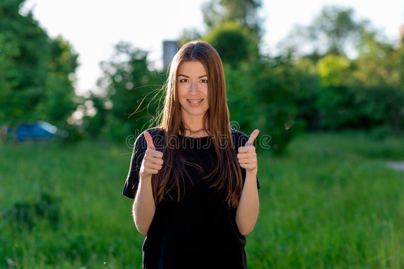 Σκοτεινός-μαλλιαρό καφετής-eyed κορίτσι Ασιάτης Το καλοκαίρι υπαίθρια Δείχνει το δάχτυλό του επάνω και με τα δύο χέρια Συγκίνηση  στοκ εικόνα
