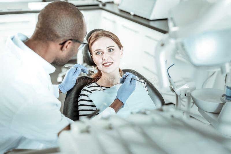 Σκοτεινός-ξεφλουδισμένος γιατρός που συνεργάζεται με τον όμορφο ασθενή του στοκ φωτογραφίες