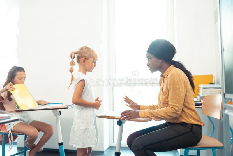 Σκοτεινός-ξεφλουδισμένος δάσκαλος που μιλά με το χαριτωμένο κορίτσι που φορά το άσπρο φόρεμα στοκ φωτογραφίες