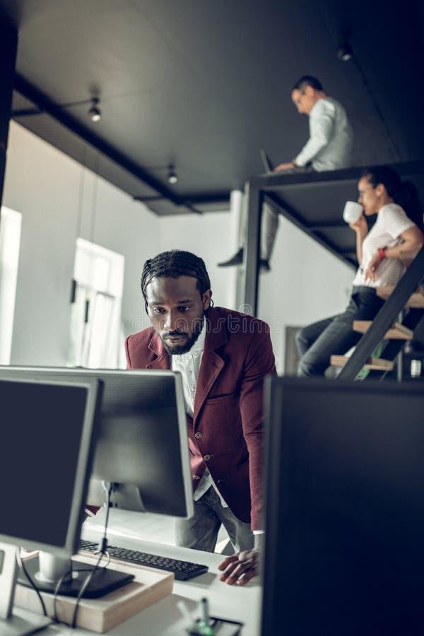 Σκοτεινός-ξεφλουδισμένος επιχειρηματίας που εξετάζει την οθόνη του υπολογιστή στοκ φωτογραφία