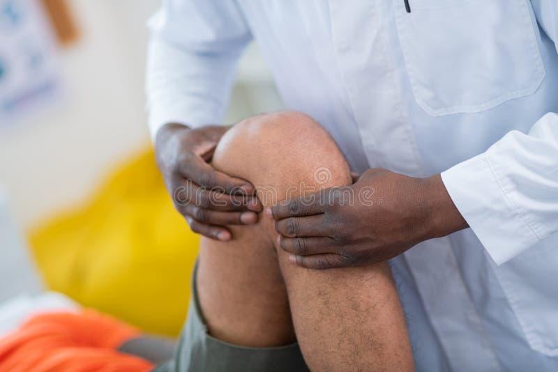 Σκοτεινός-ξεφλουδισμένος θεράπων σχετικά με το πόδι του αθλητικού τύπου που έρχεται σε τον στοκ εικόνα