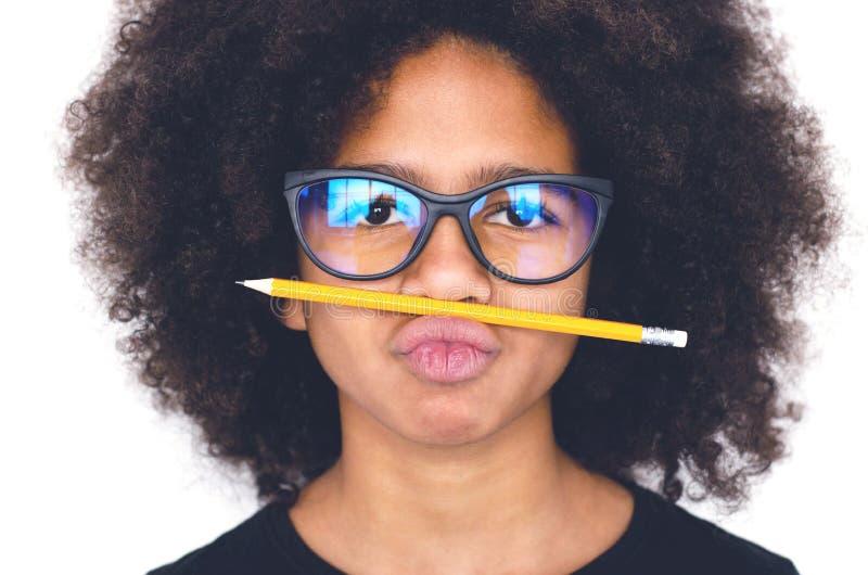 Σκοτεινός-ξεφλουδισμένο κορίτσι με τα γυαλιά που κρατά ένα απλό μολύβι στοκ εικόνες με δικαίωμα ελεύθερης χρήσης