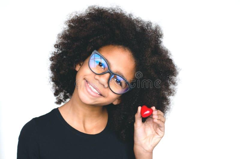 Σκοτεινός-ξεφλουδισμένο κορίτσι με τα γυαλιά που κρατά μια κόκκινη καρδιά στοκ εικόνες με δικαίωμα ελεύθερης χρήσης