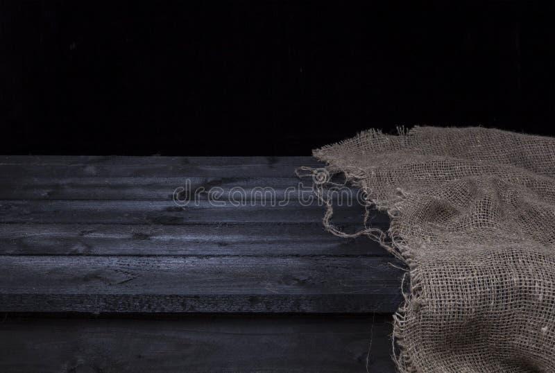 Σκοτεινός ξύλινος πίνακας με burlap για το montage επίδειξης προϊόντων, μαύρο ξύλινο εσωτερικό στοκ φωτογραφία με δικαίωμα ελεύθερης χρήσης