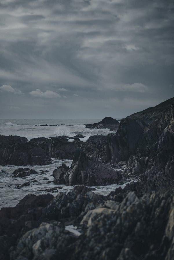 Σκοτεινός πυροβολισμός των υγρών κυμάτων που χτυπούν μια δύσκολη παραλία τη νύχτα με τα γκρίζα σύννεφα στοκ εικόνες με δικαίωμα ελεύθερης χρήσης
