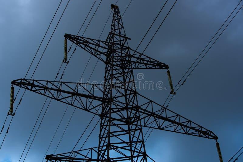 Σκοτεινός πύργος μετάδοσης με τα καλώδια υψηλής τάσης από κάτω από στοκ εικόνα με δικαίωμα ελεύθερης χρήσης
