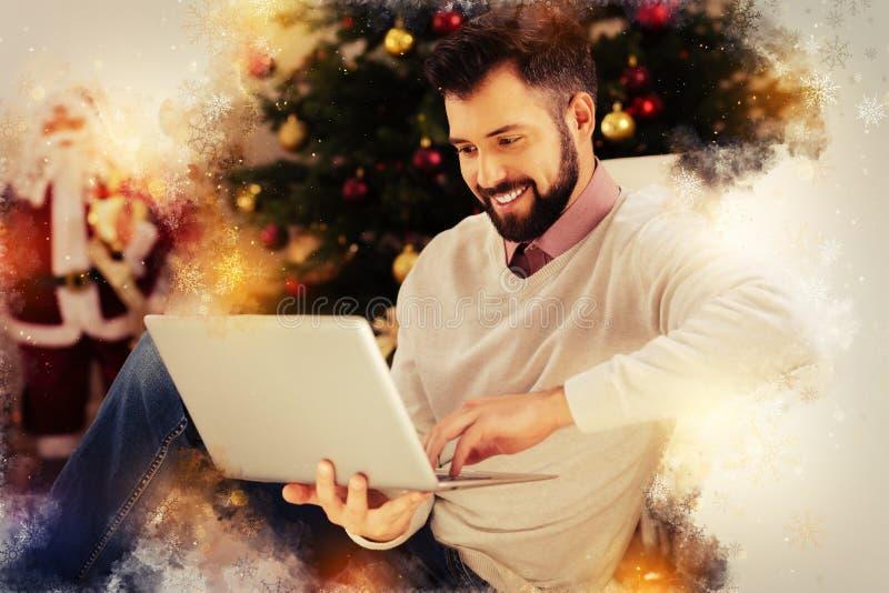 Σκοτεινός-eyed άτομο που φορά το μπεζ βίντεο Χριστουγέννων προσοχής πουλόβερ στο lap-top του στοκ εικόνα