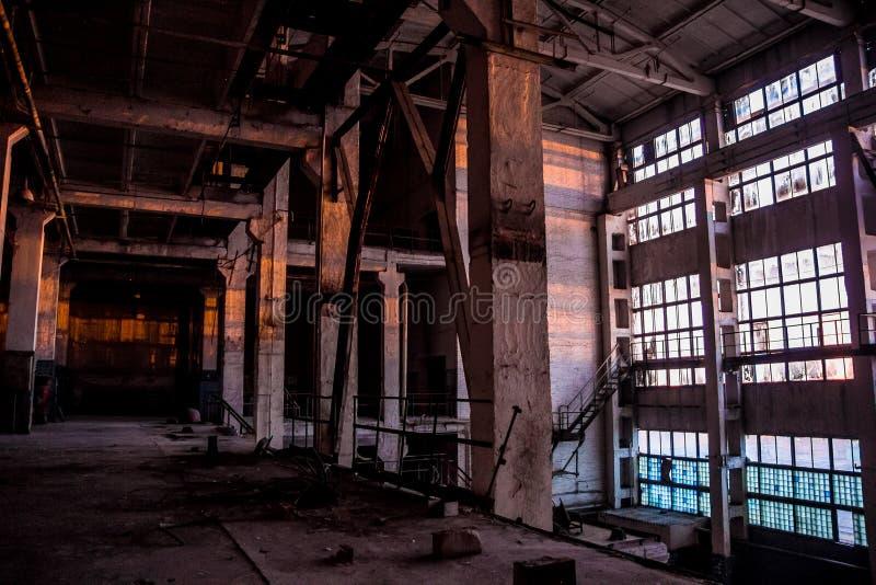 Σκοτεινό βιομηχανικό εσωτερικό της μεγάλης κενής αίθουσας για την κατασκευή ή την αποθήκευση εγκαταλειμμένο εργοστάσιο στοκ εικόνα