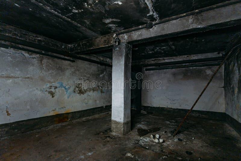 Σκοτεινό και ανατριχιαστικό βρώμικο εγκαταλελειμμένο υπόγειο μετά την πυρκαγιά Τοίχοι σε μαύρη αιθάλη στοκ φωτογραφία με δικαίωμα ελεύθερης χρήσης