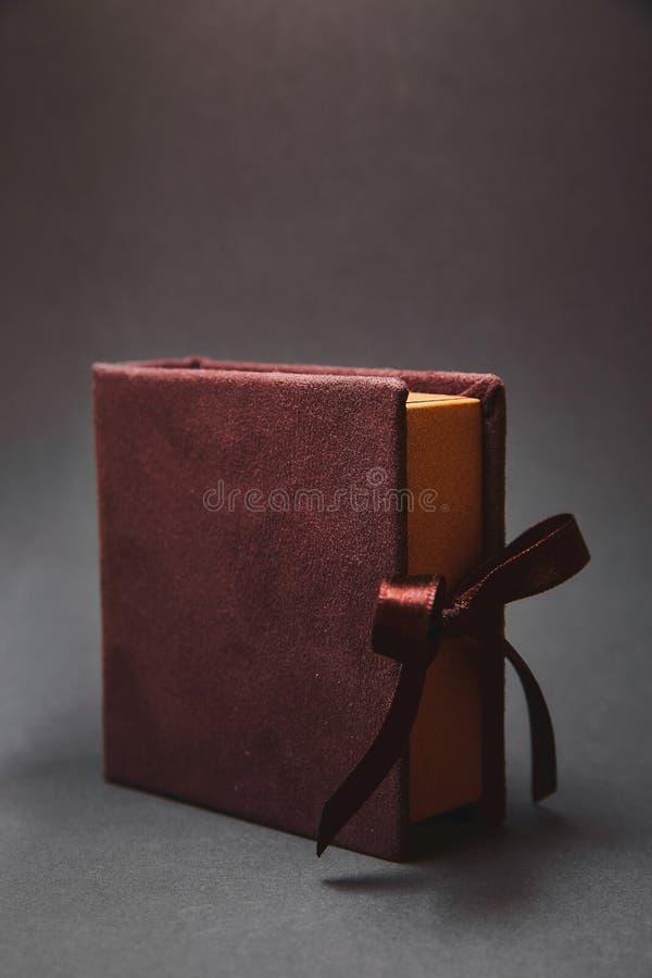 Σκοτεινό καφετί κιβώτιο για μια κίνηση λάμψης με μια κάλυψη από ένα σουέτ, που δένεται στις κορδέλλες σατέν με ένα τόξο Ένα όμορφ στοκ εικόνες με δικαίωμα ελεύθερης χρήσης