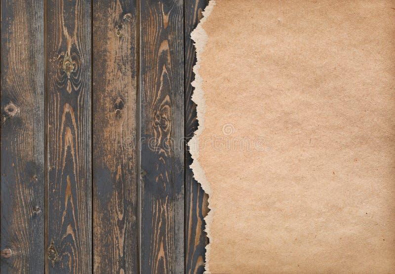 Σκοτεινό ξύλινο υπόβαθρο με το σχισμένο παλαιό έγγραφο στοκ εικόνα