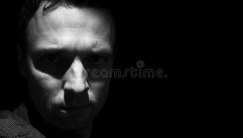 Σκοτεινό πορτρέτο κινηματογραφήσεων σε πρώτο πλάνο του νέου ενήλικου ατόμου στοκ φωτογραφία με δικαίωμα ελεύθερης χρήσης