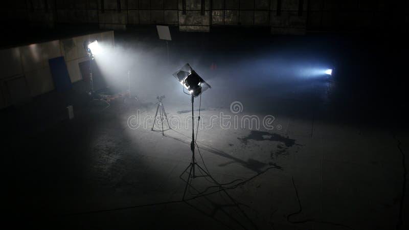 Σκοτεινό στούντιο φωτογραφιών με τα ελαφριά επίκεντρα Ευρύχωρο σκοτεινό δωμάτιο με τους παρεχόμενους προβολείς και κάμερα στο τρί στοκ φωτογραφία με δικαίωμα ελεύθερης χρήσης