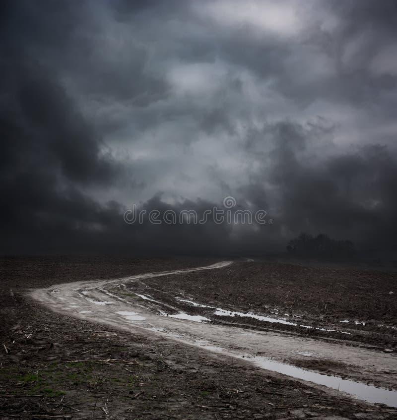Σκοτεινό τοπίο με το βρώμικο δρόμο και τον ευμετάβλητο ουρανό στοκ φωτογραφία με δικαίωμα ελεύθερης χρήσης