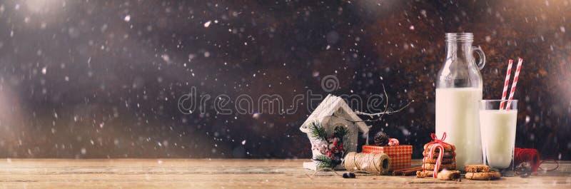 Σκοτεινό υπόβαθρο Χριστουγέννων με το χιόνι και bokeh, διάστημα αντιγράφων απαγορευμένα Μπουκάλι, γυαλί με το γάλα για Santa, μπι στοκ εικόνες με δικαίωμα ελεύθερης χρήσης