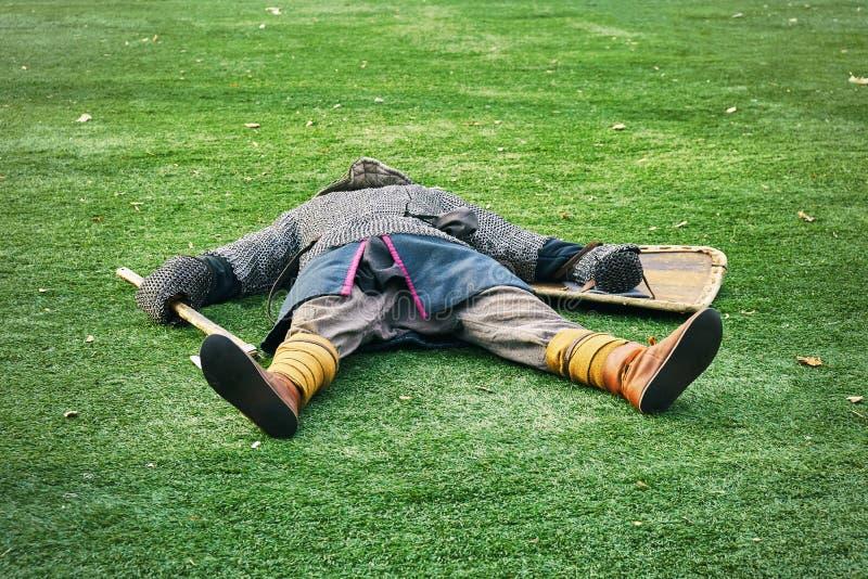 Σκοτωμένος μεσαιωνικός πολεμιστής που βρίσκεται στην πράσινη χλόη στοκ φωτογραφίες με δικαίωμα ελεύθερης χρήσης
