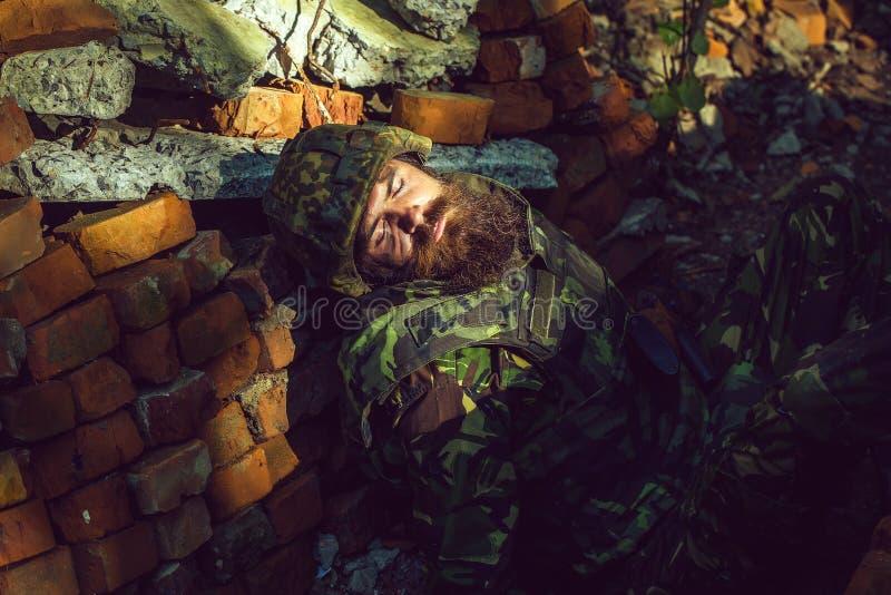 Σκοτωμένος στρατιώτης με τη γενειάδα στο πρόσωπο στην κάλυψη και το στρατιωτικό κράνος στο υπόβαθρο τούβλου πετρών στοκ φωτογραφία με δικαίωμα ελεύθερης χρήσης