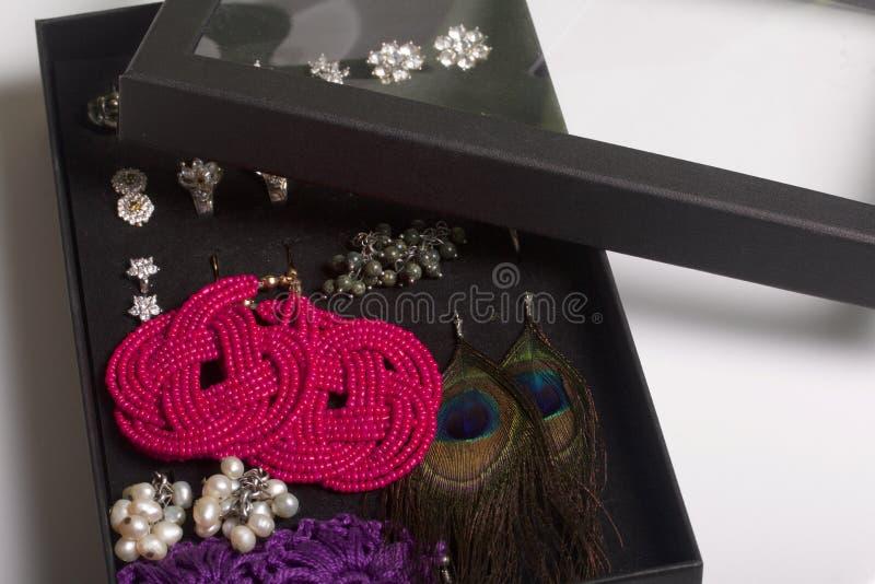 Σκουλαρίκια και δαχτυλίδια γυναικών ` s σε ένα ειδικό κιβώτιο για την αποθήκευση Μια συλλογή του κοσμήματος για τις διαφορετικές  στοκ εικόνα με δικαίωμα ελεύθερης χρήσης