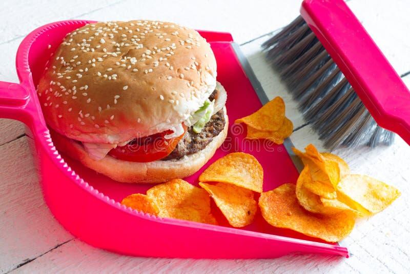 Σκουπίζοντας άχρηστο φαγητό με burger και dustpan τσιπ την έννοια της διατροφής υγείας detox στοκ εικόνα με δικαίωμα ελεύθερης χρήσης
