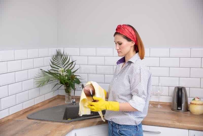 Σκουπίζοντας γυαλί γυναικών με την πετσέτα στην κουζίνα στοκ εικόνες