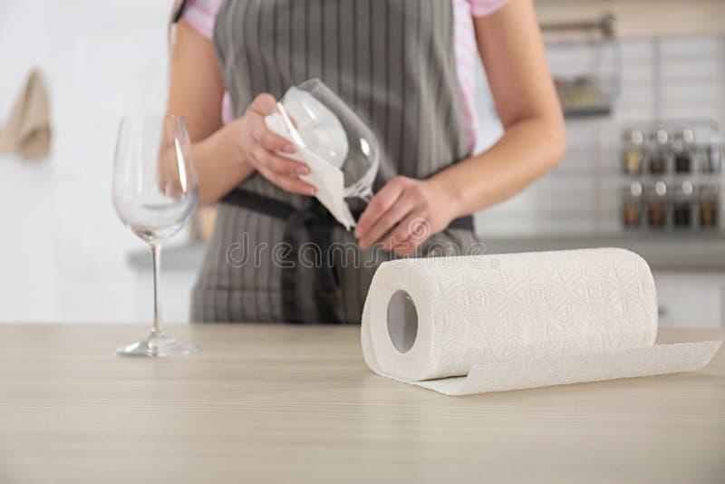Σκουπίζοντας γυαλί κρασιού γυναικών με την πετσέτα εγγράφου στην κουζίνα στοκ εικόνα με δικαίωμα ελεύθερης χρήσης