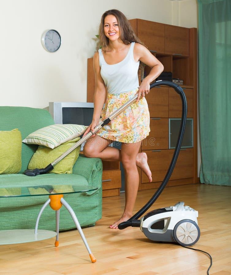 Σκουπίζοντας με ηλεκτρική σκούπα καθιστικό γυναικών στοκ φωτογραφία με δικαίωμα ελεύθερης χρήσης