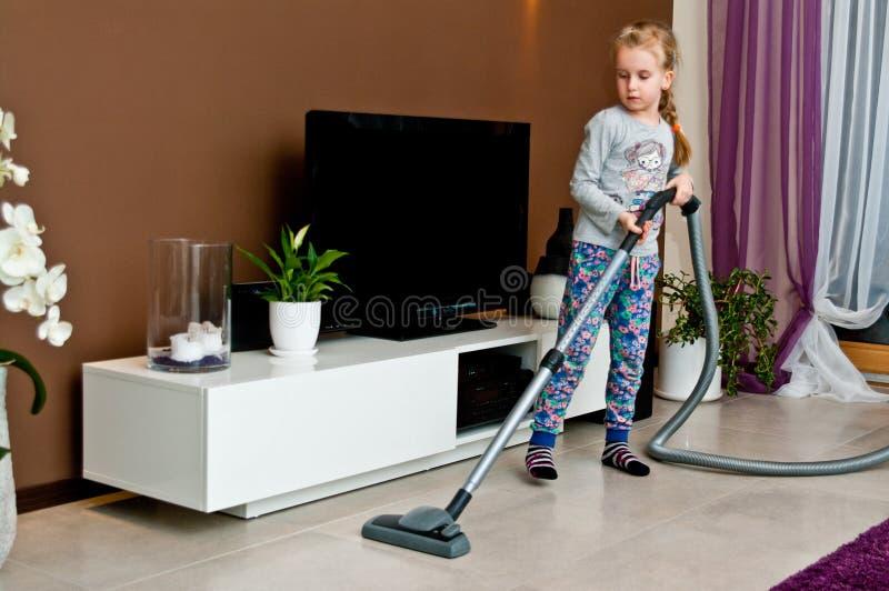 Σκουπίζοντας με ηλεκτρική σκούπα δωμάτιο νέων κοριτσιών στοκ φωτογραφία με δικαίωμα ελεύθερης χρήσης