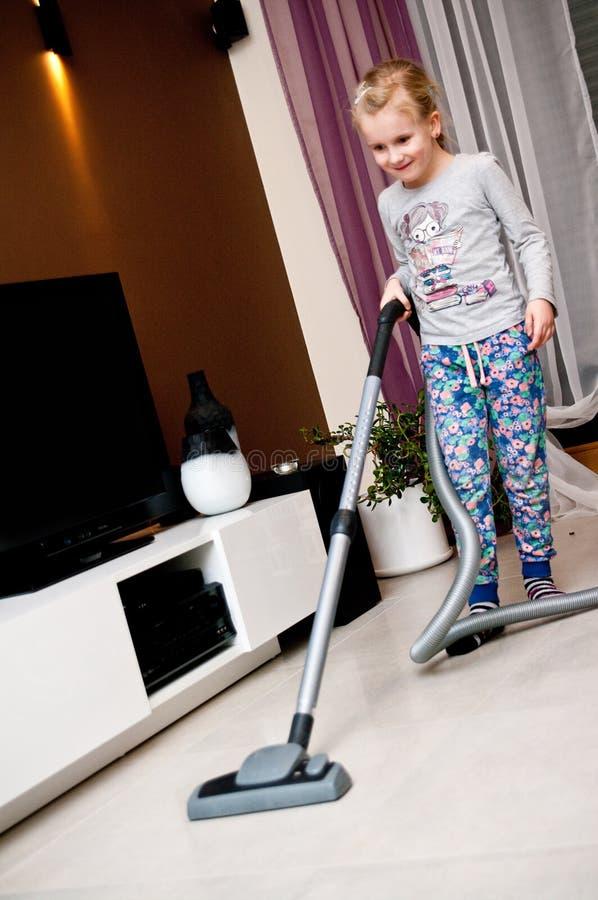 Σκουπίζοντας με ηλεκτρική σκούπα δωμάτιο νέων κοριτσιών
