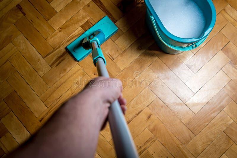 Σκουπίζοντας πάτωμα από τη σφουγγαρίστρα ψηκτρών στοκ εικόνες