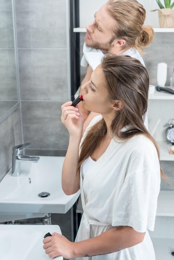 Σκουπίζοντας πρόσωπο ατόμων ενώ η σύζυγός του που εφαρμόζει το κόκκινο κραγιόν στο λουτρό το πρωί στοκ εικόνα
