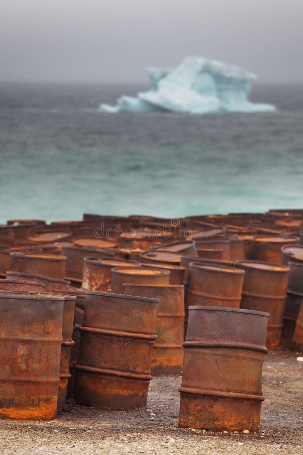 Σκουριασμένα τύμπανα στην αρκτική ακτή με το παγόβουνο στο υπόβαθρο στοκ εικόνα