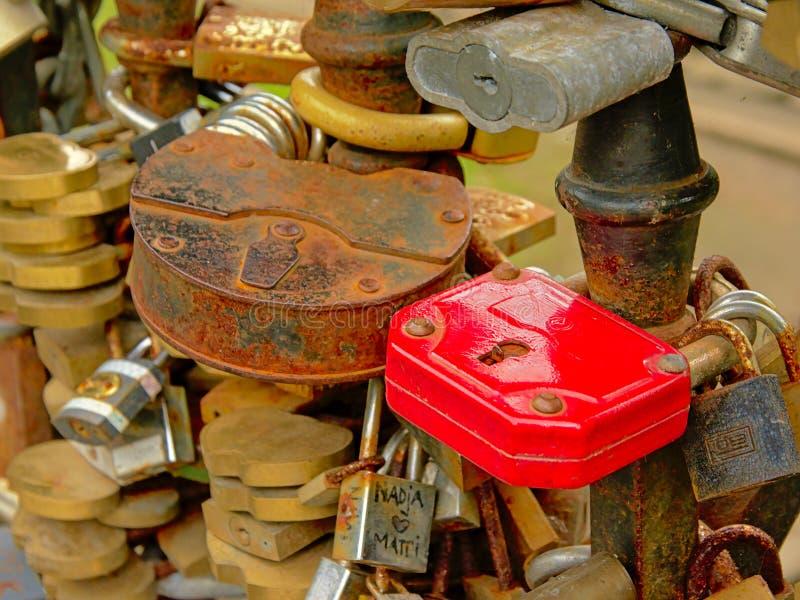 Σκουριασμένες κλειδαριές αγάπης που βρίσκονται στο κιγκλίδωμα μιας γέφυρας στη Ρήγα στοκ εικόνες