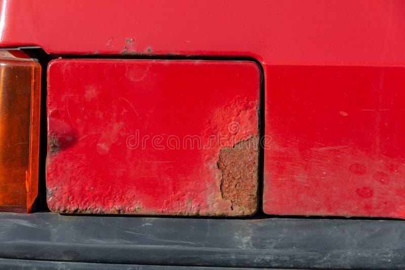 Σκουριασμένη ΚΑΠ αερίου στην πλευρά ενός παλαιού σκουριασμένου αυτοκινήτου στοκ εικόνα με δικαίωμα ελεύθερης χρήσης