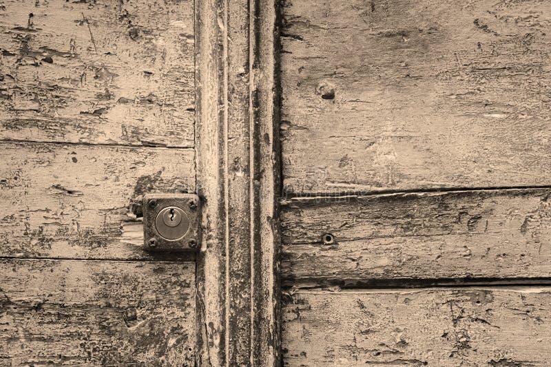 Σκουριασμένη κλειδαρότρυπα σε μια ξύλινη πόρτα σε γραπτό στοκ εικόνες