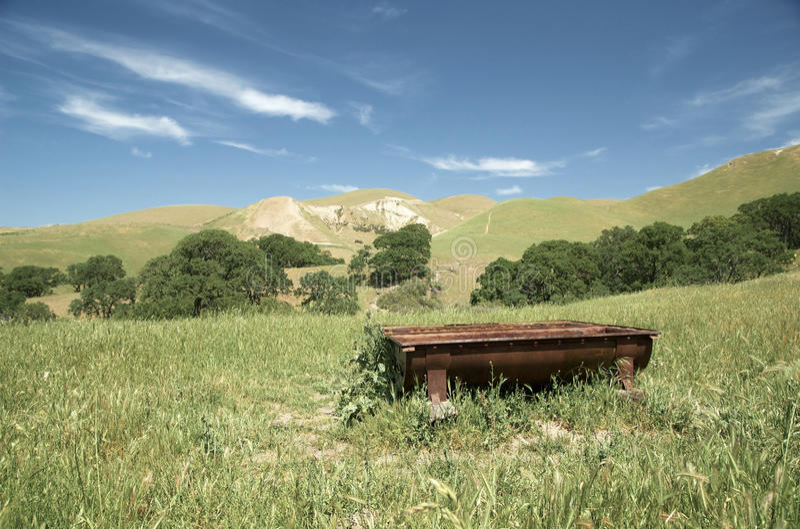 Σκουριασμένη παλαιά γούρνα νερού βοοειδών κοντά στους λόφους στοκ εικόνες