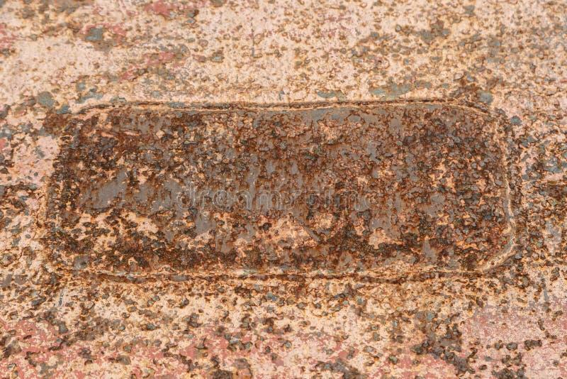 Σκουριασμένη παχιά επιφάνεια μετάλλων με το υπόλειμμα χρωμάτων και ένα ορθογώνιο ενωμένο στενά πιάτο ως υπόβαθρο στοκ εικόνα με δικαίωμα ελεύθερης χρήσης