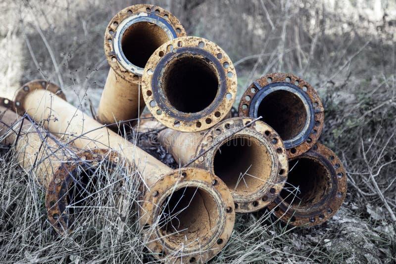 Σκουριασμένοι παλαιοί σωλήνες υπονόμων νερού στην ψηλή ξηρά χλόη στοκ φωτογραφίες