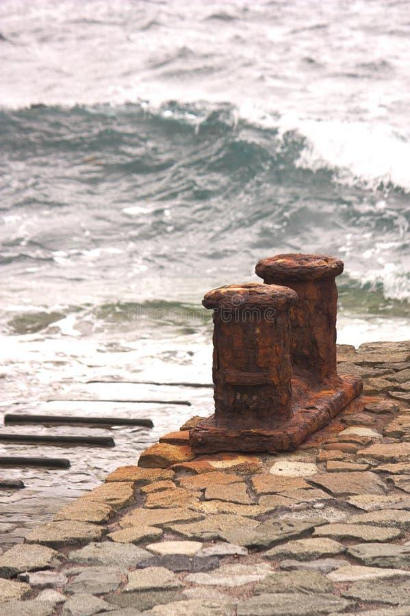 Σκουριασμένο Noray με τα ωκεάνια κύματα στο υπόβαθρο σε ένα μικρό λιμάνι στοκ εικόνες