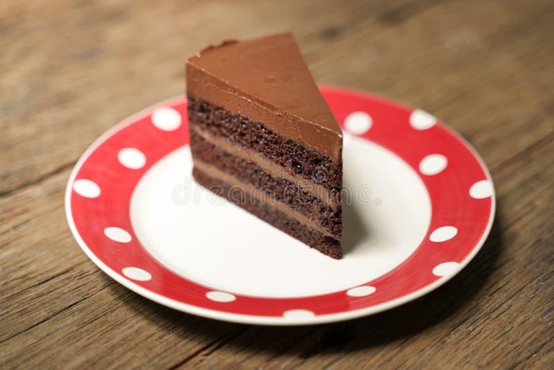 Σκούρο κέικ σοκολάτας με κόκκινη λευκή πλάκα στο ξύλινο τραπέζι στοκ φωτογραφίες