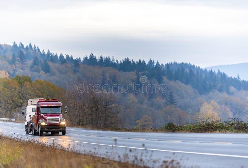 Σκούρο κόκκινο μεγάλη εγκατάσταση γεώτρησης που ρυμουλκεί το ημι ημι φορτηγό αμαξιών ημέρας φορτηγών σπασμένο ρυμούλκηση στον άνε στοκ φωτογραφίες με δικαίωμα ελεύθερης χρήσης