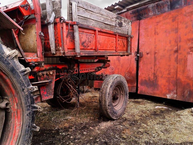 Σκούρο κόκκινο υπόβαθρο grunge με μέρος του παλαιού παραμελημένου τρακτέρ με τις λαστιχένιες βρώμικες ρόδες στοκ φωτογραφίες