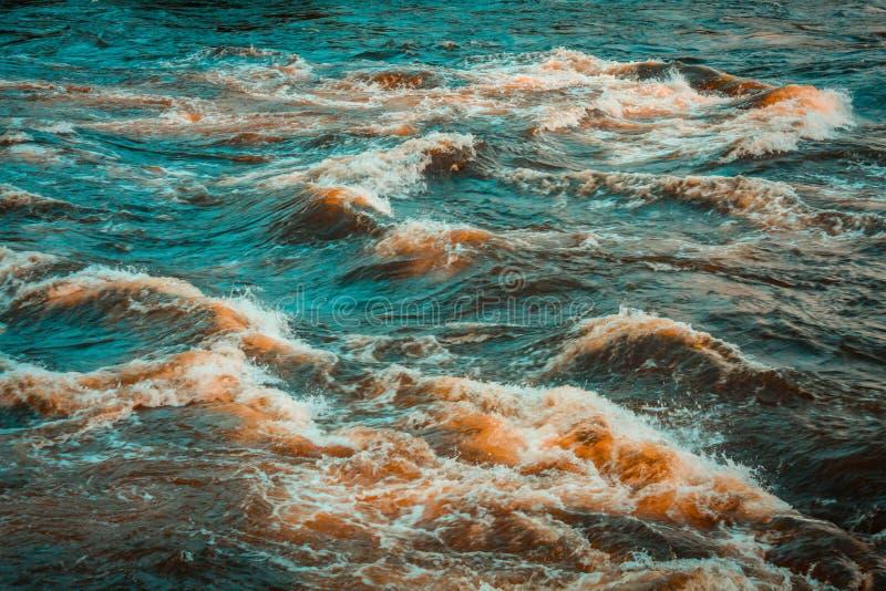 Σκούρο μπλε με την κόκκινη θυελλώδη επιφάνεια του νερού ποταμού με τον άσπρους αφρό και τα κύματα στοκ φωτογραφία